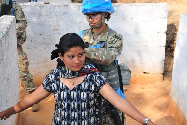 Spc. Maria Hutchinson, a military police officer with the 57th Military Police Company, 728th Military Police Battalion, 8th Military Police Brigade, performs a search on a Nepalese citizen during exercise Shanti Prayas III. Shanti Prayas is a multinational United Nations peacekeeping exercise designed to provide pre-deployment training to U.N. partner countries in preparation for real-world peacekeeping operations. (U.S. Army photo by Staff Sgt. Michael Behlin)