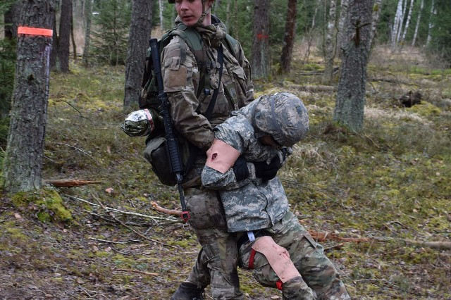 GRAFENWOEHR, Germany. -- A participant evacuates a casualty from the battlefield during Expert Field Medical Badge (EFMB) testing, 27 March, in the Grafenwoehr Training Area (GTA). More than 200 participants will test their skills and endurance over the next three days to win for themselves the coveted badge. The pass rate is traditionally less than 18 percent. The Expert Field Medical Badge is awarded to military personnel who complete a variety of physical, mental and written tests that determine their ability to quickly, accurately and effectively perform complex life-saving medical tasks while in a variety of hostile environments and situations. The EFMB is considered the medical equivalent of the Expert Infantryman's Badge, but is statistically harder to earn than the EIB. This year's EFMB is hosted by the 212th Combat Support Hospital, 30th Medical Command. The more than 200 U.S. and NATO servicemembers vying for the badge come from posts across Europe.