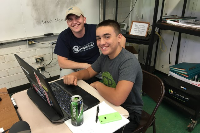 Army Spec. Evan Wittman, a cryptologic network warfare specialist, Detachment-Hawaii (DET HI), 782nd Military Intelligence Battalion (MI BN), mentors a Leilehua High School Junior Reserve Officer Training Corp (JROTC) cadet who is participating in the school's CyberPatriot program.