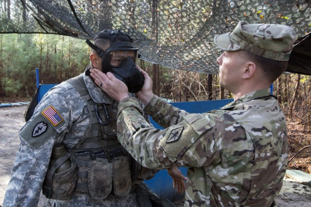 Staff Sgt. James Ferguson, with Bravo Company, Special Troops Battalion, checks the seal on the protective mask of  Staff Sgt. Frankie Berdecia Rodriguez, with Alpha Company, 3rd Battalion, 39th Infantry Regiment, during train up for the Fort Jackson Expert Infantryman Badge competition March 22. Ferguson is one of the graders for the event.