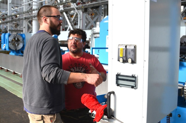 Machinist Christopher Herold, left, is discussing the proving-out process with machine installer Franco Morlino.