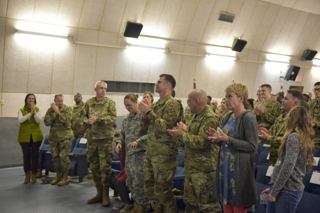 The crowd stands up to clap for Maj. Lisa Jaster for her great speech at the Women's History Month Observance that took place at Camp Henry Theater on Mar. 28.