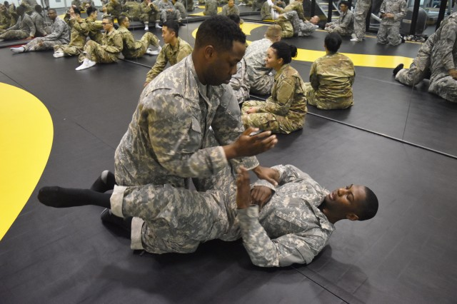 Spc. Deandre Parker and Pfc. Teion Middleton goes against each other at the end of the combatives physical training on Mar. 20.