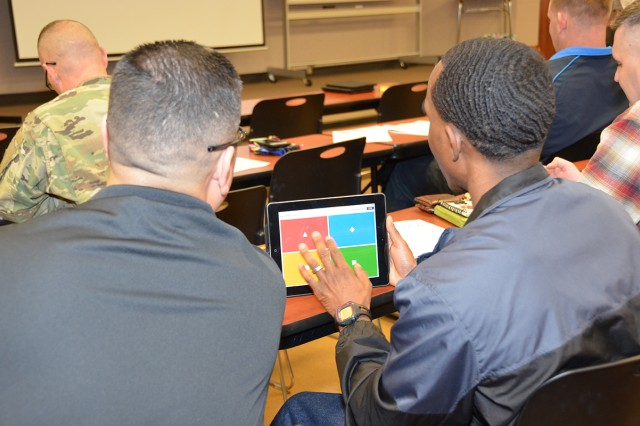 Right, Sgt. 1st Class Vincent Green, Co. B., 84th Chem. Bn. incoming first sergeant, uses an online platform student engagement tool during the workshop as 1st Sgt. Carlos Gomez, Co. C, 84th Chem. Bn. looks on.