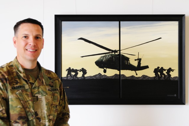 CW4 James Hagerty, an Aviation accident investigator with the U.S. Army Combat Readiness Safety Center and UH-60 Black Hawk pilot, stands with the painting, 'Infill,' displayed on the second floor of the U.S. Army Aviation Museum.