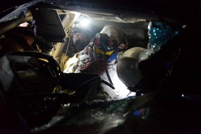 Rescuers provide oxygen and secure a neck brace to a victim trapped in a vehicle before extrication and transport during platoon validations with the 911th Technical Rescue Engineering Company March, 29, 2017, at the Center for National Response in Gallagher, West Virginia.