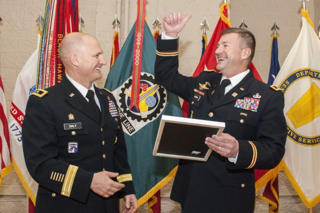 Maj. Gen. Edward Daly, senior commander at Rock Island Arsenal and commanding general, U.S. Army Sustainment Command, presents Col. Lance Koenig, former chief of staff, ASC, a letter from Jerry Jones, owner and president of the Dallas Cowboys Organization, during a retirement ceremony for Koenig in Heritage Hall, Rock Island Arsenal, Illinois, March 28.