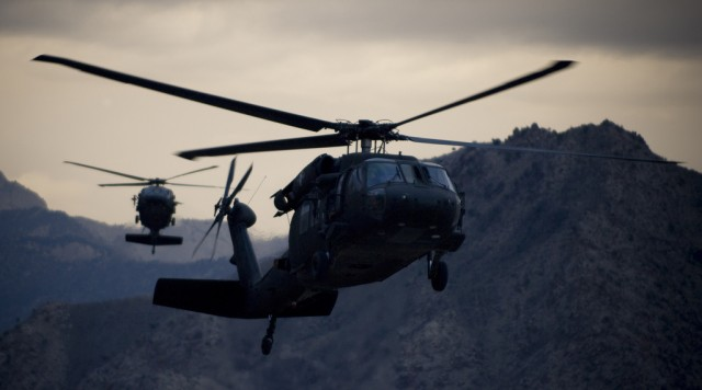 Two Army UH-60 Black Hawk helicopters prepare for landing
