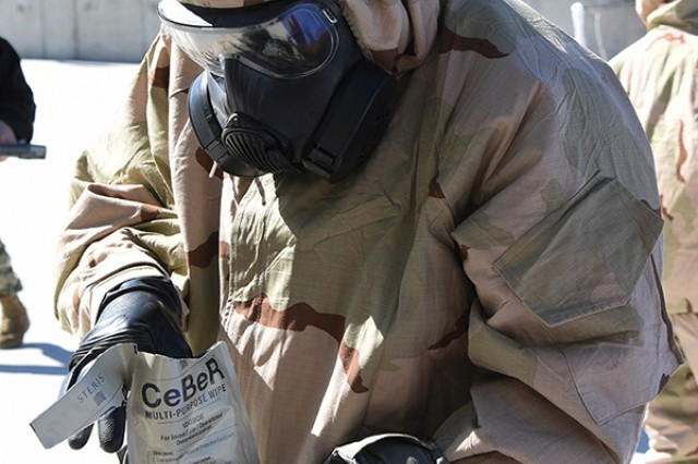 A Soldier removes one of five moist towelettes from a Joint Services Equipment Wipe packet at Dugway Proving Ground, Utah, before removing simulated chemical agent from sensitive equipment. The March 28, 2017 test scenario began deep in the desert with a simulated chemical agent attack and quick field decontamination, then included a 4-mile drive to this decontamination pad for continued use of the JSEW while evaluators took notes.