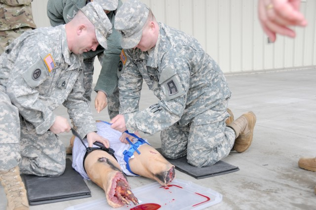 Sgt. 1st Class Joshua Park (left) and Staff Sgt. Jonathan Zurek practice applying a tourniquet and other medical techniques during annual training for Headquarters and Headquarters Detachment, First Army U.S. Army Reserve Support Command, at Fort McCoy, Wis., on March 30.