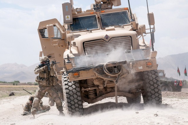 A U.S. Army paratrooper with the 82nd Airborne Division's 1st Brigade Combat Team fires his M4 carbine at insurgents during a firefight June 30, 2012, Ghazni Province, Afghanistan. The vehicle he is using for cover is a Mine Resistant Ambush Protected vehicle.