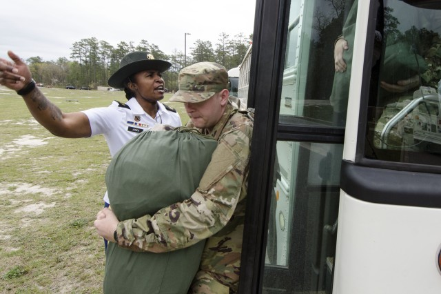 "Staff Sgt.  Elease Jones, a drill sergeant with Charlie Company, 3rd Battalion, 34th Infantry Regiment, motivates a Soldier in Training to hurry off the bus from the 120th Adjutant General Battalion (Reception) and head towards the company area April 3. The 3-34 Infantry has been designated the ""Centennial Battalion"" because their unit will graduate basic training on the day of Fort Jackson's Centennial Celebration."