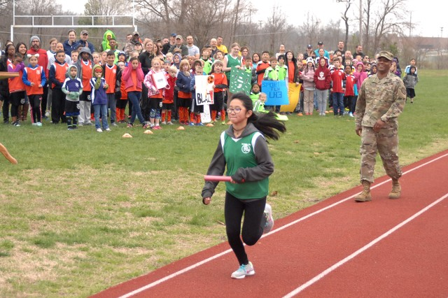 Team Lightning track-and-field athlete Jasmine Torres, 12, takes the ceremonial first relay hand-off of the 2017 season from Col. Tracy Lanier, U.S. Army Garrison Fort Leonard Wood commander, during Saturday's Youth Sports Soccer and Track Opening Ceremony at Gerlach Field.