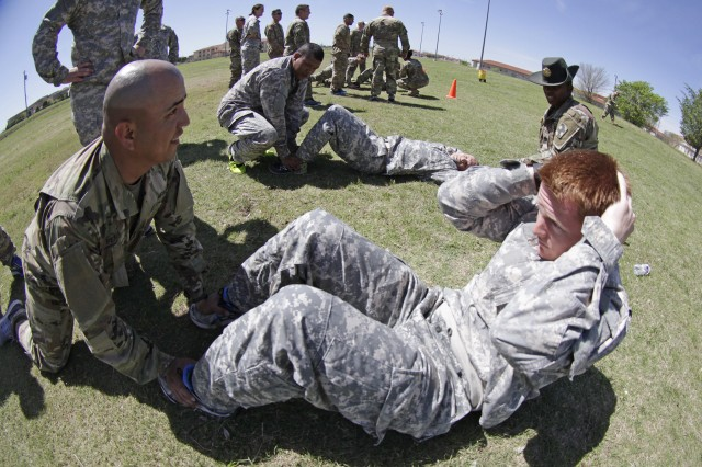 Capt. Orlando Pena, A/1-40th FA commander,  holds the feet of Capt. Brett Jack, C/1-40th commander, during the sit-ups challenge.