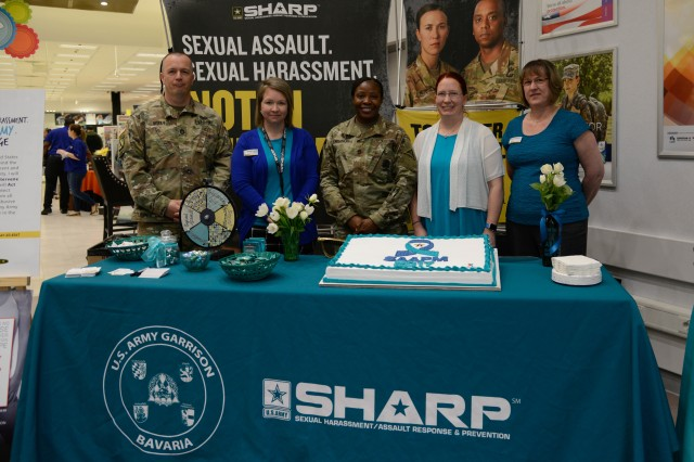 (From left to  right) U.S. Army Sgt. 1st Class Timothy Utter, assigned to the 16th Sustainment Brigade; Meghan Huff, Victim Advocate for U.S. Army Garrison Bavaria; U.S. Army Sgt. 1st Class Justina Emmanuel, assigned to the  7th Army Training Command (ATC) as , lead sexual assault response coordinator; Trinity Peterson, Victim Advocate for 7th ATC; and Kathy Johnson, Victim Advocate for U.S. Army Garrison Bavaria; pose for a group photo at their booth at the Tower Barracks Exchange, April 4, 2017. This kick-off event for Sexual Assault Awareness and Prevention Month informs Soldiers, civilians and family members about sexual harassment and assault.