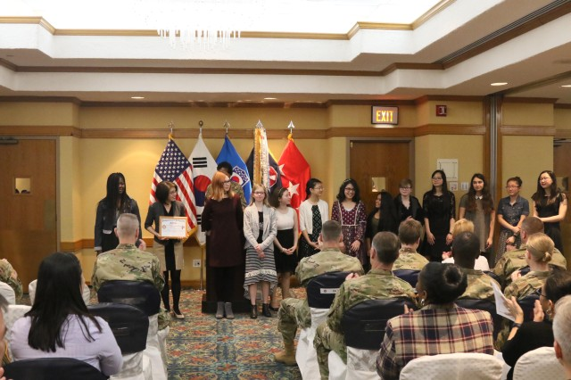 Seoul American Middle School Choir receives a recognition at the end of Women's History Month Observance at Dragon Hill Lodge, Yongsan Garrison. The choir performed the Korean and U.S. national anthems during the event.