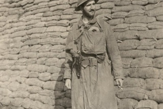 "Lt. Archibald Robert Allen, 48th Battalion, standing in front of a wall of sandbags. Lt. Allen is wearing a trench coat and pair of rubber boots. Original caption reads ""After Passchendaele."" One of a series of images in an album relating to the wartime service of Lieutenant Harry Downes MC MM, 48th Battalion."