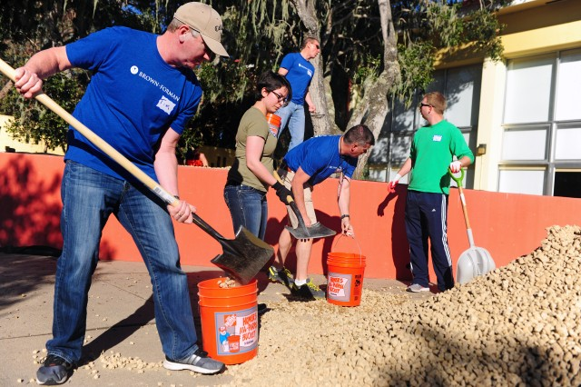 PRESIDIO OF MONTEREY, California -- Employees of the Kentucky-based spirit corporation Brown-Forman partner with military volunteers moving rocks for landscaping during a beautification project at General Stilwell Community Center on March 14 as part of the corporation's Service Day event.