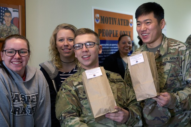 When exercise Key Resolve ended and they returned from the field Pfc. Samuel C. Burton (left) and Pfc. Hur, Sung-ju (right) were welcomed home by family members (from left to right) Olivia Jones, Michelle Graham and Natasha Williams. The spouses were part of the battalion's Family Readiness Group that prepared 400 snack bags of snacks for the returning Soldiers.
