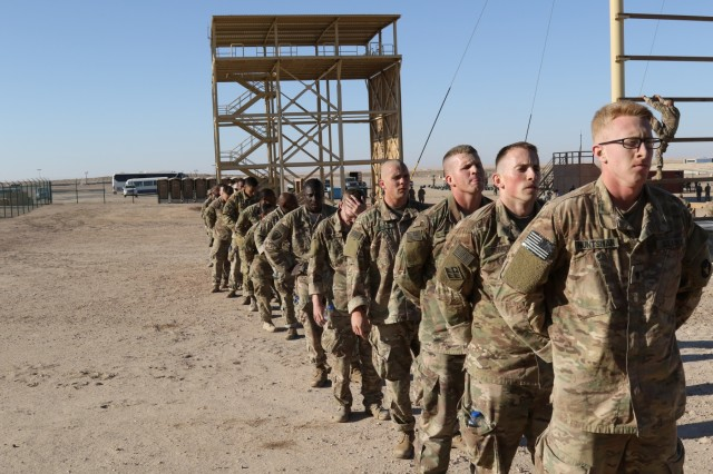 "U.S. Servicemembers line up to complete the confidence climb obstacle (right), during day zero of U.S. Army Central's first Air Assault Course, April 4, 2017, at Camp Beuhring, Kuwait. The Air Assault Course is a 12-day class that allows U.S. military personnel in the USARCENT theater of operations the unique opportunity to become air assault qualified, while deployed outside the continental United States.  ""Once completed, the perspective student goes on to become the subject matter expert to their company or unit commander assisting them with planning for air assault operations into whatever environment they may need,"" said Capt. Ronald Snyder, Company B commander, Army National Guard Warrior Training Center."