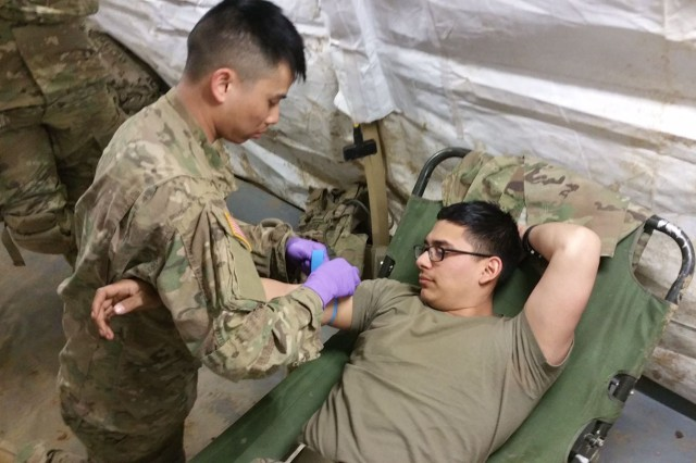 U.S. Army Spc. Gary Tran, medical personnel, C Troop, Regimental Support Squadron, 2d Cavalry Regiment (left), prepares Sgt. Eric Lorado for blood collection during a Regimental Support Area defensive exercise in Grafenwoehr Training Area Feb 28, 2017. Soldiers conducted blood collection training in order to validate RSA defensive procedures and mass casualty operations within 2CR RSA in preparation for the upcoming Saber Junction 17.