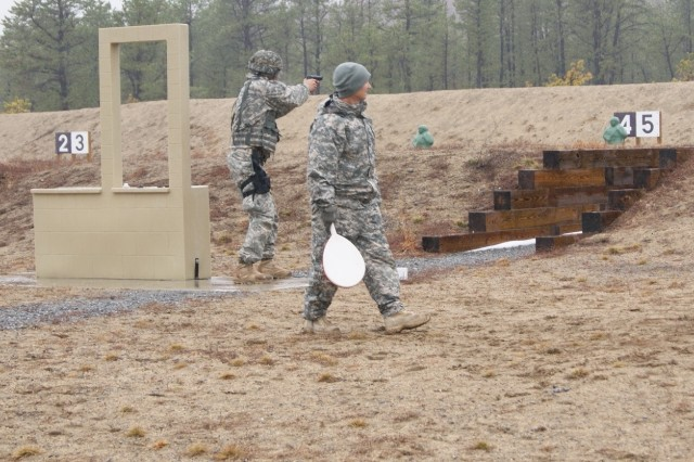 (Background) A competitor fires a 9mm pistol at the qualification course as a range safety officer (foreground) checks for safety issues at Fort Devens, Massachusetts, April 4, 2017, as part of the 2017 Joint 80th Training Command and 99th Regional Support Command Best Warrior Competition.