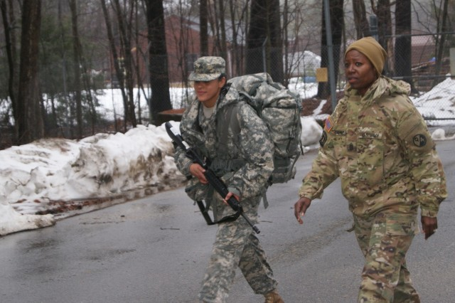 (Right) Command Sgt. Maj. Sharon Campbell motivates competitor Sgt. Nicole Paese as she nears the end of the 6.2-mile ruck march at Fort Devens, Massachusetts, April 4, 2017, as part of the 2017 Joint 80th Training Command and 99th Regional Support Command Best Warrior Competition.