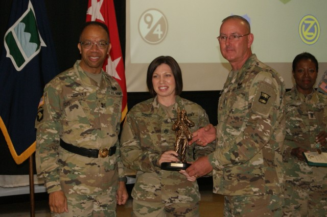 (Left) Maj. Gen. A.C. Roper, commanding general of the 80th Training Command, and Command Sgt. Maj. Jeff Darlington (right), command sergeant major of the 80th, award Staff Sgt. Marcy DiOssi (center) as the Best Warrior at the 2017 Joint 80th TC and 99th Regional Support Command Best Warrior Competition awards ceremony at Fort Devens, Massachusetts, April 6, 2017. (Background) Command Sgt. Maj. Sharon Campbell, command sergeant major of the 94th Training Division, looks on.