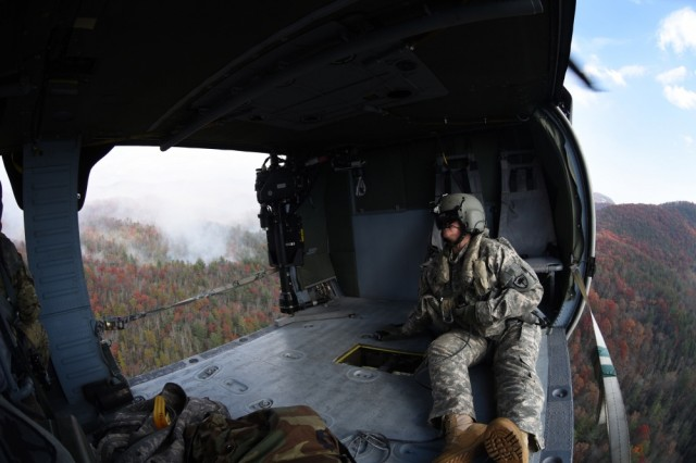 Army Staff Sgt. Jessica Thibeau, with the South Carolina Army National Guard's 59th Aviation Troop Command, observes from a UH-60 Black Hawk helicopter during efforts to fight South Carolina wildfires, Nov. 24, 2016.