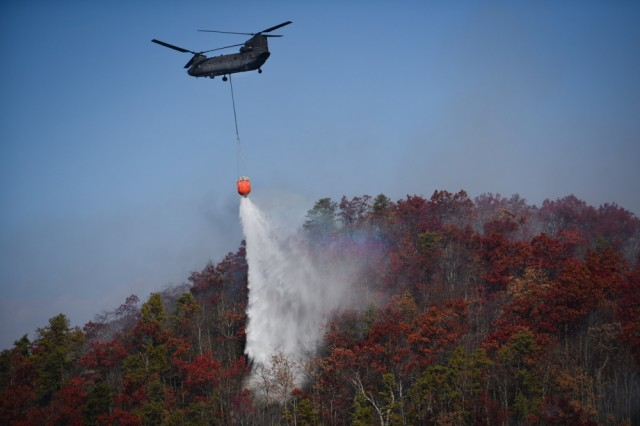A CH-47 Chinook helicopter from the South Carolina Army National Guard's 59th Aviation Troop Command drops water from a bucket firefighting system during efforts to fight South Carolina wildfires, Nov. 24, 2016.