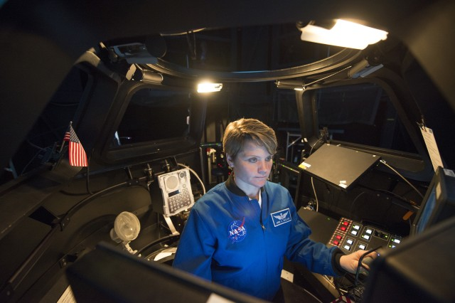 Maj. Anne McClain, one of two active-duty Army astronauts, looks out of a mock cupola, a multi-windowed observatory attached to the International Space Station, as she simulates bringing in a cargo load in space with the station's robotic arm during training at Johnson Space Center in Houston March 1, 2017. Cargo loads, which are launched every six months or so, normally deliver food, clothing and science experiments to the crew.
