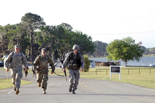 (Left to right) Spc. Charles Robertson, Sgt. David Robbins and Sgt. Samuel Johnson, with Company C, 1st Battalion, 168th Infantry, of Johnston, Iowa, approach the finish line of the 12-mile ruck march during the final day of the Expert Infantry Badge (EIB) testing phase at Camp Blanding in Starke, Florida, on April 6. Iowa Army National Guard Soldiers with the 2nd Brigade Combat Team, 34th Infantry Division and Minnesota Army National Guard Soldiers with the 1st Brigade Combat Team, 34th Infantry Division -- each sporting the 34th Infantry Division Red Bull patch -- traveled to Florida to participate in more than 30 rigorous events in pursuit of the prestigious EIB. Robertson, who was previously disqualified from the course and Robbins, who earned his badge several years ago, finished the march with Johnson to motivate him to the finish line.