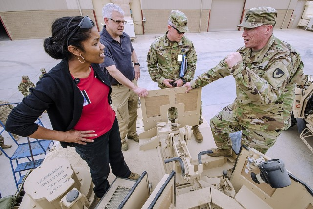 Steffanie Easter, acting assistant secretary of the Army for acquisition, logistics and technology talks about combat capabilities with Sgt. 1st Class Frank Taylor, contract officer representative, Army Field Support Battalion-Kuwait atop an M1 Abrams Tank during her visit to the 401st Army Field Support Brigade at Camp Arifjan, Kuwait, April 11. (U.S. Army Photo by Justin Graff, 401st AFSB Public Affairs)