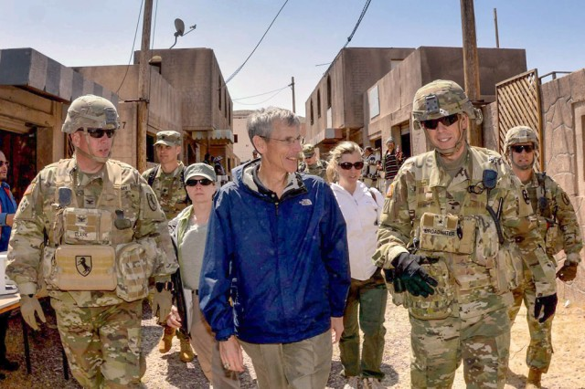 Honorable Robert M. Speer, acting Secretary of the U.S. Army, escorted by Brig. Gen. Jeff Broadwater, Commander of the National Training Center and Col. Joseph Clark, Commander of the 11th Armored Cavalry Regiment, walk through the mock village known as Razish, where role players engaged in the selling of goods and services, National Training Center, April 8.
