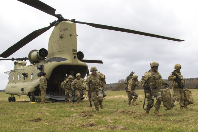 Soldiers from 3rd Squadron, 2nd Cavalry Regiment, quickly exit a CH-47 Chinook helicopter from B Company, 3-10 General Support Aviation Battalion during a joint-training exercise April 6 at Grafenwoehr Training Area, Germany. By training together early on, later and larger Atlantic Resolve exercises will benefit from increased knowledge and understanding by aviators and Soldiers alike.