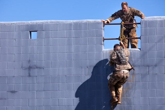 U.S. Army Rangers 1st Lt. Matthew Slocum and 1st Lt. Christopher Gaziano, assigned to the 10th Mountain Division, maneuver over an obstacle April 7 during the 34th Annual David E. Grange Jr. Best Ranger Competition at Fort Benning, Ga. The Best Ranger Competition is a three-day event consisting of challenges to test Soldiers' physical, mental and technical capabilities. It places the military's best two-man Ranger teams against each other to compete for the title of Best Ranger.