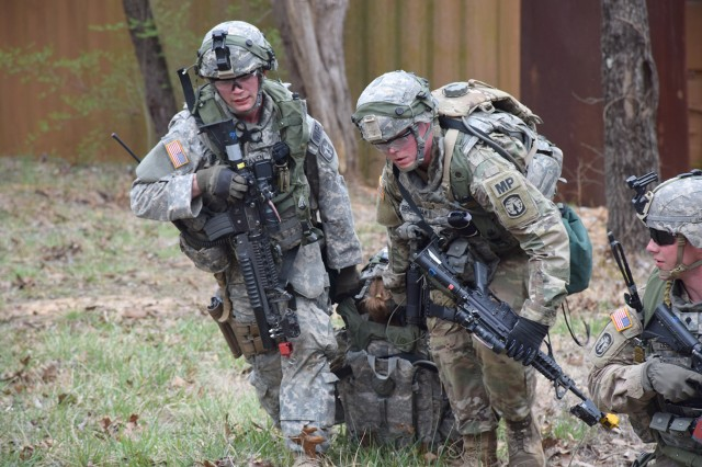 "Soldiers from 3rd Platoon, 23rd Military Police Company, drag a team leader who was ""injured"" during a search for a high-value target in the village during training at Fort Knox, Ky."