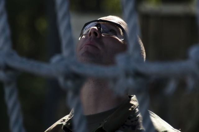 A Soldier in Training with Bravo Company, 3rd Battalion, 34th Infantry Regiment, looks up to ensure his fellow Soldiers are crawling down a cargo net during training at Fort Jackson's Victory Tower. The Soldiers who are in their first week of Basic Combat Training are learning the confidence needed in later stages of training. The Battalion is known as the Centennial Battalion because it will graduate during the post's Centennial Celebration in June.