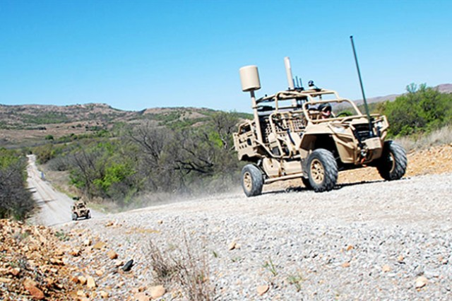 The Hunter (right) and Killer vehicles drive up a road toward the experimentation area of the Maneuver Fires Integrated Experiment (MFIX), April 3, at Fort Sill.