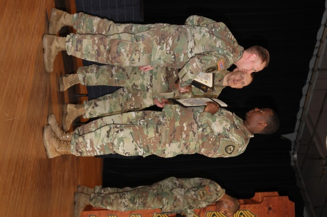 FORT GEORGE G. MEADE, MD -- Sgt. Daniel Goodman (right), Echo Company, 782nd Military Intelligence Battalion (E/782), receives a copy of the NCO Creed and the NCO Charge signifying entry into the noncommissioned officer Corps from Command Sgt. Maj. Brian Cullen (center), the garrison command sergeant major for Fort George G. Meade, and 1st Sgt. Stanley Collins (left), the first sergeant for E/782.