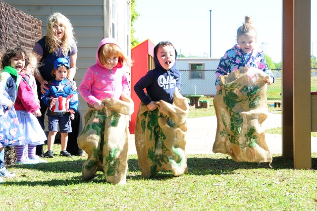 Children take part in a sack race on the new playground at the Fort Rucker Child Development Center April 7.