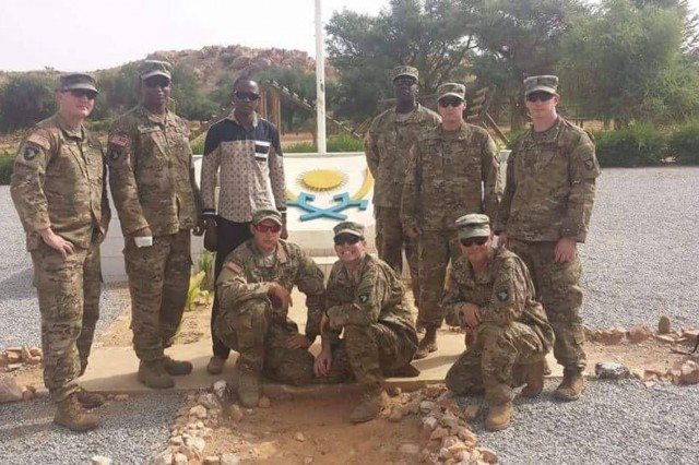 "The team from 2nd Battalion, 327th Infantry Regiment, of the 1st Brigade Combat Team ""Bastogne"", 101st Airborne Division (Air Assault), poses in front of the Nigerien Armed Forces basic training crest.The Bastogne Brigade team spent four weeks observing and making recommendations for improvement to the Nigerien basic training course.Standing from left to right: Sgt. 1st Class Michael Mullins, Staff Sgt. Cameron Marsh, Interpreter Mr. Abdourahmane Ibrahim, Sgt. 1st Class Elocious Frazier, Sgt. 1st Class Sean Carey, 1st Lt. Dan Godlasky. Kneeling from left to right: Staff Sgt. Matthew England, Staff Sgt. Andrew Prince, First Sgt. Peter Russell.Photo taken by Moussa Moumouni."