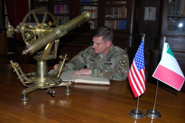 Col. Steve Marks, U.S. Army Garrison Italy commander, signs the distinguished guests book after a professional development visit and partner nation engagement at the Istituto Geografico Militare (Military Geographic Institute) in Florence March 23. Also shown in the photo is an 18th century telescopic theodolite, an optical instrument for measuring both horizontal and vertical angles and used for topographic surveying.
