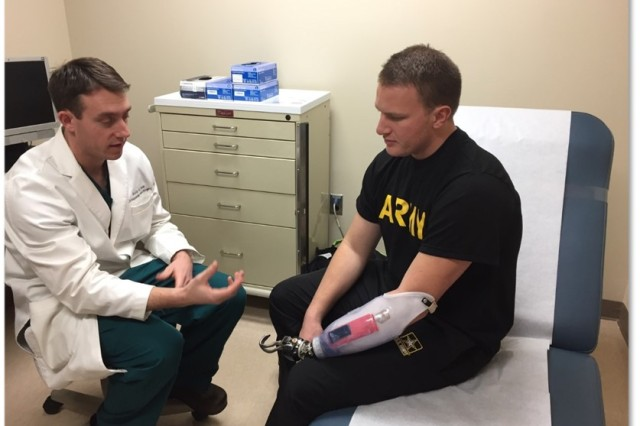 Healthcare Professional at Walter Reed chats with Wounded Warrior SSG Weidner about his recovery.