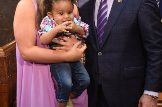 Louisiana Governor John Bel Edwards stands with Mallory Ott, daughter of Louisiana National Guard Chief Warrant Officer Five Charles Ott, Jr., who is holding Carter Gray, son of Maj. Ebony Carter, after signing a proclamation that recognized April as Month of the Military Child at the state Capitol in Baton Rouge, April 12, 2017.