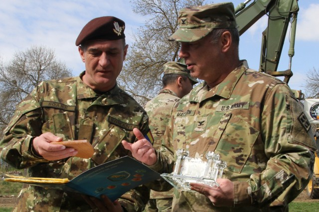U.S. Army Col. Paul Mattern, commander of the 926th Engineer Brigade, and Romanian Brig. Gen. Gheorghe Soare, commander of the Romanian 10th Engineer Brigade, exchange gifts after the opening ceremony for Resolute Castle 2017 at Cincu Training Center, Romania on April 14. The commanders emphasized a strong sense of unity and cohesion for their respective forces working together as a new cycle of Resolute Castle begins. Bonds of friendship like this showcase the effectiveness of Operation Atlantic Resolve, a NATO mission involving the U.S. and Europe in a combined effort to enhance bonds of friendship and deter aggression. (Photo by Army Pvt. Nicholas Vidro, 7th Mobile Public Affairs Detachment)