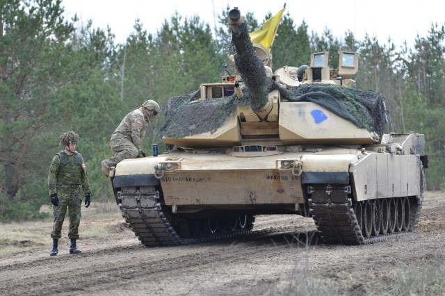 Lt. Col. Stephen Capehart, the battalion commander for 1st Battalion, 68th Armor Regiment, 3rd Armored Brigade Combat Team, 4th Infantry Division, Fort Carson, Colo., climbs onto his Abrams on a range in Adazi Military Base, Latvia, April 14. Lt. Col. Wade Rutland, the commanding officer for 1st Battalion, Princess Patricia's Canadian Light Infantry (1 PPCLI), Canadian Forces Base Edmonton, Alberta, prepares to mount the Abrams as well. The 3rd ABCT is deployed to eastern Europe under Operation Atlantic Resolve, a U.S. led NATO endeavor to promote peace in the region by deterring aggressive actions. The Canadians are preparing to lead Latvia in NATO's latest operation, Enhanced Forward Presence, which features four multinational battalion battle groups in Poland, Latvia, Lithuania and Estonia. (U.S. Army photo by Sgt. Shiloh Capers)