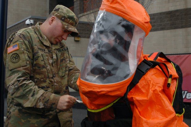 2nd Civil Support Team (CST) member Staff Sgt. David Hansen (left) helps fellow team member Staff Sgt. Joshua Spagnola don a hazmat suit during the 2nd CST's training exercise at Joseph L. Bruno Stadium in Troy, N.Y. on April 12, 2017. Team members are trained to identify chemical, biological, and radiological agents and advise first-responders on how to deal with these materials.