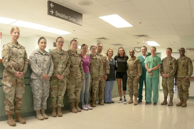 Capt. Kelly Elmlinger (center), an Army nurse and cancer survivor, visits William Beaumont Army Medical Center's Surgical Ward, where she shared her experience during her fight with synovial sarcoma, a rare soft-tissue cancer, and recovering through limb salvage and amputation  with staff members, April 6. Elmlinger, who is coaching and mentoring wounded warriors during this year's Department of Defense Warrior Games, visited with staff members to help them understand the impact WBAMC staff can have on patients.