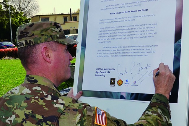 U.S. Army Africa Commander Maj. Gen. Joseph P. Harrington signs the Month of the Military Child Proclamation at Villaggio Youth Center March 30 at the conclusion of the MOMC kickoff celebration.